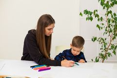 Mother and young son draws a picture at the table. Mother and young son draws a picture royalty free stock photography