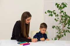 Mother and young son draws a picture at the table. Mother and young son draws a picture royalty free stock photos