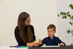 Mother and young son draws a picture at the table. Mother and young son draws a picture royalty free stock images