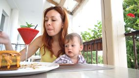 Mother and young son are eating in the restaurant stock video footage