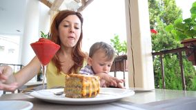 Mother and young son are eating in the restaurant stock video