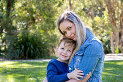 Mother and young son embracing shile sitting outdoors on beautif. Ul day wearing casual clothing stock photography