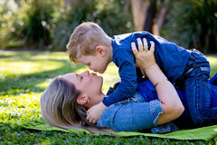 Mother and young son embracing and about to kiss whilst playing. On rug in park stock images