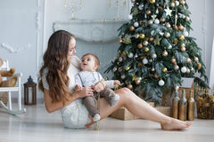 Mother and young son at home near Christmas tree Royalty Free Stock Photography