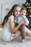 Mother and young son at home near Christmas tree Royalty Free Stock Image