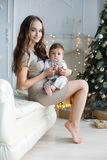 Mother and young son at home near Christmas tree. Happy brunette women with long hair,dressed in a short beige dress,conducts the new year`s holiday sitting on a Stock Photography