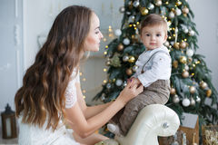 Mother and young son at home near Christmas tree. Happy brunette women with long hair,dressed in a short beige dress,conducts the new year`s holiday sitting on a Stock Image