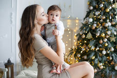 Mother and young son at home near Christmas tree. Happy brunette women with long hair,dressed in a short beige dress,conducts the new year`s holiday sitting on a Royalty Free Stock Photo