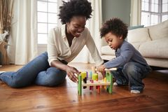 Mother And Young Son Playing With Wooden Toy At Home royalty free stock image