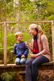 Mother and young son sitting on a bridge in a forest Stock Images