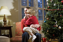 Mother and young son sitting by Christmas tree Royalty Free Stock Photos