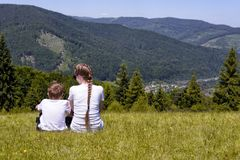 Mother and young son sitting on grass on the background of coniferous forest and mountains royalty free stock images