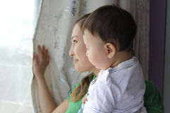 Mother and son looking in window Royalty Free Stock Images