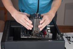 Motherboard des Einsatzes ATX des jungen Mannes zum Computerkasten Stockbilder