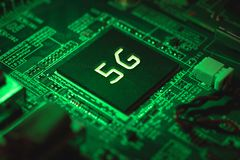 5g chip closeup on motherboard. Green light. stock photo