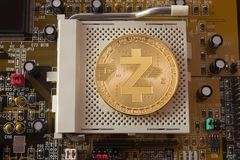 Crypto currency gold coin zcash on a motherboard. On a motherboard is gold coin of a digital crypto  currency - zcash Royalty Free Stock Image