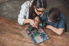 Little son and his mother in protective glasses working with soldering iron stock photos