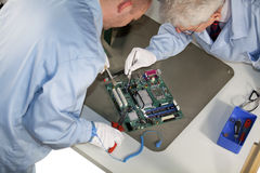 Motherboard repairs. IT - engineers doing repairs and cleaning on a motherboard Stock Photography