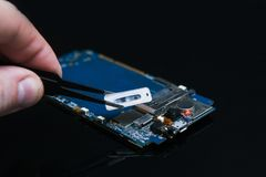 Motherboard repairs mending gadgets phones. Motherboard repairs on black background. professional mending of smartphones, gadgets and other electronic devices Stock Photos