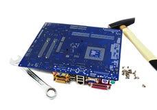 Motherboard van de computer met moersleutel en hamer Stock Afbeeldingen