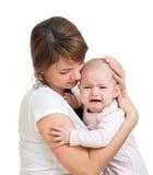 Mothercalming il suo bambino gridante isolato Immagini Stock