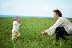 Motherhood. Mother walking with her baby in spring green field Royalty Free Stock Photography