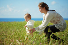 Motherhood. Mother walking with her baby in spring green field Royalty Free Stock Photos