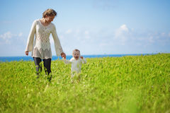 Motherhood. Mother walking with her baby in spring green field Stock Images
