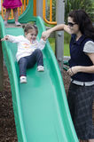 Motherhood Baby Sliding Down Slide Stock Image