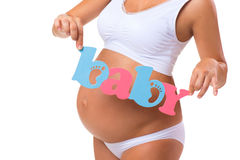 motherhood Blauwe en roze woordbaby dichtbij de zwangere buik Tweelingen, meisje of jongen Royalty-vrije Stock Fotografie