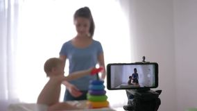 Motherhood blog, young mom blogger with child plays developing toys while recording training video on smartphone for stock video footage