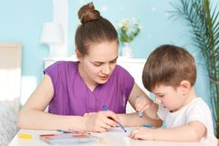 Motherhood and children concept. Photo of affectionate mother spends time with son, being in maternity leave, teaches her little m. Ale kid to draw, pose stock photos