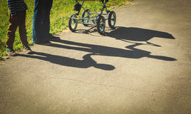 Motherhood concept- shadow of young mother holding little son and stroller Royalty Free Stock Photo
