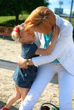 Motherhood. Daughter kid hugging mother kiss summer sweet Stock Photography