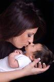 Motherhood joy. Beautiful mother kissing her newborn baby boy Stock Photos