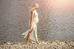 Motherhood and maternity concept Mother with big belly expecting baby. Pregnancy and fertility. Pregnant woman in white dress walking on sea beach on sunny day Stock Photos