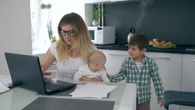 Motherhood, mom with baby in her arms scolds her son who interferes with working at home