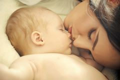 Motherhood. Mother and baby sleep in bed Stock Photography
