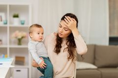 Tired mother with baby boy at home Royalty Free Stock Photography
