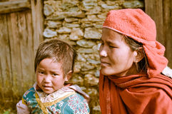 Motherhood in Nepal. Beni, Nepal - circa May 2012: Photo of mother in red scarf and headcloth kneeling next to her small daughter with brown hair and brown eyes Stock Images