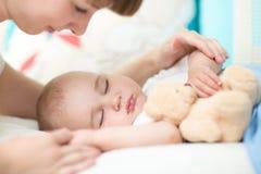 motherhood parenthood Mãe nova que olha seu bebê que dorme na cama fotos de stock royalty free