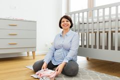 Happy pregnant woman with baby clothes at home royalty free stock image