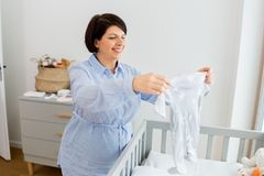 Happy pregnant woman setting baby clothes at home stock image