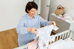 Happy pregnant woman setting baby clothes at home. Motherhood, pregnancy and nursery concept - happy pregnant middle-aged woman reviewing baby clothes on bed at royalty free stock photos