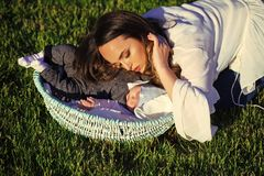 Motherhood. Woman sleep with infant child boy in basket outdoor. Mother hug baby son asleep in crib on green grass. Mothers day concept. Family, love stock photo