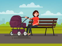 Motherhood. Young mother sitting on a bench with a pram in the p Stock Image