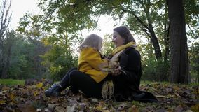 Motherly care, young mother hugs her beloved joyful daughter tightly while sitting on lawn covered with foliage while
