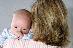 Motherly Love. Mother holding newborn boy on her shoulder Stock Image