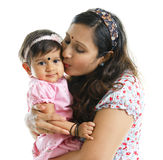 Motherly love. Asian Indian mother kissing her baby girl, isolated on white background Royalty Free Stock Photos
