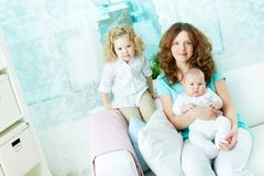 Motherly love. Lovely women and her two infants sitting on sofa at home Stock Photography